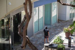 CINDY ELLEN RUSSELL / CRUSSELL@STARADVERTISER.COM                                 A shopper Thursday walked past shuttered retail storefronts at the International Market Place in Waikiki.