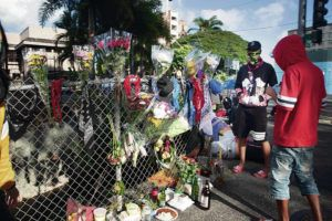 GEORGE F. LEE / GLEE@STARADVERTISER.COM                                  Mourners of the 16 year old shot by police on Monday gathered at the corner of Kalakaua Avenue and Philip Street on Wednesday, April 7.