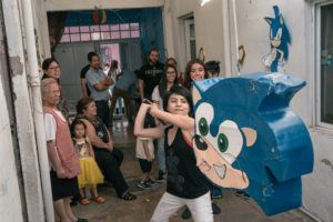 NEW YORK TIMES / APRIL 4                                 Kelly Portillo Cortez, 13, hits a Sonic the Hedgehog piñata during their youngest brother's party at their home in Mexico City.