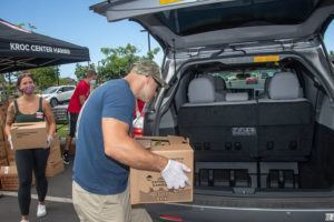 CRAIG T. KOJIMA / MAY 28                                 Sydne Walters, left, and Robert Sigmon, load a trunk with boxes of fresh produce, milk, eggs and other food items. The Salvation Army's Kroc Center Hawaii held a drive-thru food distribution event from 10 a.m. to 11:30 a.m. Friday in Ewa Beach serving approximately 500 families facing food insecurity during the coronavirus pandemic.