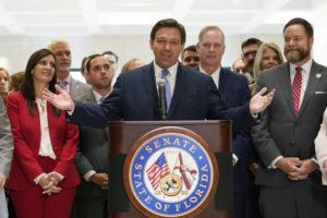 ASSOCIATED PRESS                                 Surrounded by lawmakers, Florida Gov.Ron DeSantis spoke at the end of a legislative session, Friday, at the Capitol in Tallahassee, Fla.