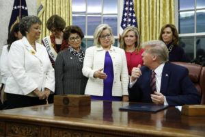 ASSOCIATED PRESS / 2019                                 Rep. Liz Cheney, R-Wyo., center, speaks with President Donald Trump during a bill signing ceremony for the Women's Suffrage Centennial Commemorative Coin Act in the Oval Office of the White House in Washington.