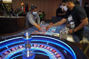 ASSOCIATED PRESS                                 People wore face masks, in July 2020, as a precaution against the coronavirus as they played roulette on the Fourth of July at the Strat hotel-casino in Las Vegas. Some Las Vegas Strip casinos have been allowed to open at 100% capacity, officials said today, after showing Nevada state regulators that at least 80% of their employees have received at least one shot of coronavirus vaccine.