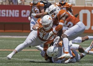 ASSOCIATED PRESS / APRIL 24                                 Texas defenders Jake Ehlinger, left, and B.J. Foster, right, tackle Kayvontay Dixon (16) during the first half of the Orange and White spring scrimmage college football game in Austin, Texas.