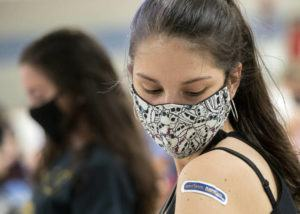 ASSOCIATED PRESS / APRIL 8                                 Kent State University student Regan Raeth, of Hudson, Ohio, looks at her vaccination bandage as she waits for 15 minutes after her shot in Kent, Ohio.