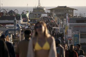 ASSOCIATED PRESS                                 People crowded the Santa Monica Pier, April 7, in Santa Monica, Calif. Teams of experts are projecting COVID-19's toll on the U.S. will fall sharply by the end of July, according to research released by the government Wednesday.