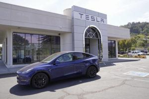 ASSOCIATED PRESS / APRIL 2                                 Two women in an electric car drive into a Tesla delivery location and service center in Corte Madera, Calif.