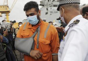 ASSOCIATED PRESS                                 People rescued by the Indian navy from a barge that sank in the Arabian sea walk out from Indian naval ship INS Kochi in Mumbai, India, Wednesday.