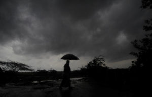 ASSOCIATED PRESS                                 A villager walks holding an umbrella as dark clouds loom over during a drizzle in Balasore district in Odisha, India, today. Tens of thousands of people were evacuated in low-lying areas of two Indian states and moved to cyclone shelters to escape a powerful storm barreling toward the eastern coast.