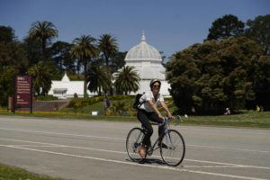 ASSOCIATED PRESS                                 A woman on a bicycle rides along the car-free John F. Kennedy Drive in Golden Gate Park with the Conservatory of Flowers in the background on April 28 in San Francisco. At the start of the pandemic, San Francisco closed off parts of a major beachfront highway and Golden Gate Park to cars so that people had a safe place to run and ride bikes. Open space advocates want to keep those areas car-free as part of a bold reimagining of how U.S. cities look. But opponents decry the continued closures as elitist, unsafe and nonsensical now that the pandemic is over and people need to drive again.