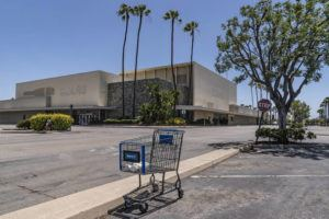 ASSOCIATED PRESS                                 An empty shopping cart in an empty parking lot at the closed Sears in Buena Park Mall in Buena Park, Calif., on Thursday.