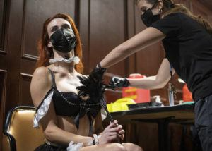 """ELLEN SCHMIDT/LAS VEGAS REVIEW-JOURNAL VIA AP                                 JoJo Hamner, a cast member of the """"Sexxy After Dark: Where Dinner Meets Play"""" show, gets the Pfizer COVID-19 vaccine during a pop-up vaccine clinic at Larry Flynt's Hustler Club on Friday, May 21, in Las Vegas."""