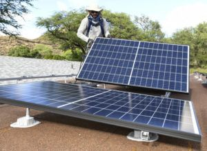 STAR-ADVERTISER / 2019                                 Marco Bernard puts into place one of the 33 solar panels on the roof of a solar electricity customer's garage.