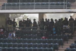 CINDY ELLEN RUSSELL / 2019                                 Baseball fans seek shelter at Les Murakami Stadium during a bout of showers during a game.