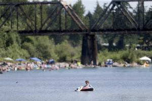 DAVE KILLEN/THE OREGONIAN VIA AP                                 People gather at the Sandy River Delta, in Ore., to cool off during the start of what should be a record-setting heat wave. The Pacific Northwest sweltered Friday as a historic heat wave hit Washington and Oregon, with temperatures in many areas expected to top out 25 to 30 degrees above normal in the coming days.