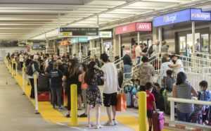 CINDY ELLEN RUSSELL / CRUSSELL@STARADVERTISER.COM                                 A large crowd gathered at the rental car kiosks in Daniel K. Inouye International Airport on March 15.