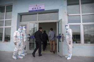 ASSOCIATED PRESS                                 Security officers in protective suits hold the doors as government officials enter the visitors' hall at the Urumqi No. 3 Detention Center in Dabancheng in western China's Xinjiang Uyghur Autonomous Region on April 23.