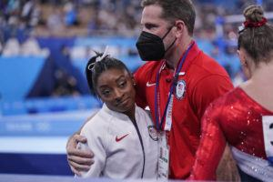 ASSOCIATED PRESS                                 Coach Laurent Landi embraces Simone Biles, after she exited the team final at the Summer Olympics today in Tokyo. The 24-year-old reigning Olympic gymnastics champion Biles huddled with a trainer after landing her vault. She then exited the competition floor with the team doctor.