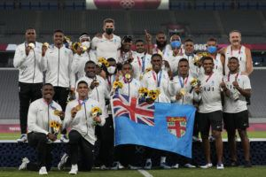 ASSOCIATED PRESS                                 Fiji players and team staff poses with their gold medals and a national flag after winning men's rugby sevens at the 2020 Summer Olympics on Wednesday.