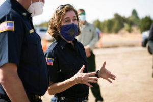ARDEN BARNES/THE HERALD AND NEWS VIA ASSOCIATED PRESS                                 Oregon Gov. Kate Brown visited the Bly Fire Camp, June 28, on the southern edge of the Bootleg Fire, in Klamath County, Ore. People in Oregon, regardless of vaccination status, will be once again be required to wear masks in most public outdoor settings, including large outdoor events where physical distancing is not possible, beginning Friday.