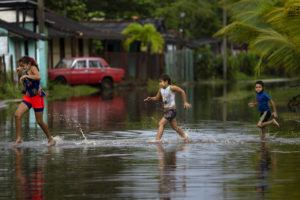 ASSOCIATED PRESS                                 Children run in a flooded street caused by rains brought on by Hurricane Ida, in Guanimar, Artemisa province, Cuba.