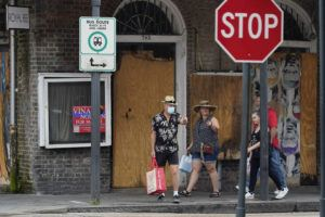 ASSOCIATED PRESS                                 Visitors walk past a French Quarter business with windows boarded in preparation Hurricane Ida on Saturday in New Orleans.