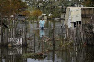 ASSOCIATED PRESS                                 A man walks down a flooded street in the aftermath of Hurricane Ida in Lafitte, La.