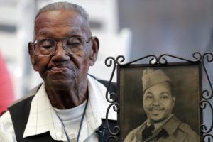 ASSOCIATED PRESS                                 World War II veteran Lawrence Brooks held a photo of himself taken in 1943, as he celebrated his 110th birthday, in September 2019, at the National World War II Museum in New Orleans. Brooks celebrated his 112th birthday, Sunday, with a drive-by party at his New Orleans home hosted by the National War War II Museum.