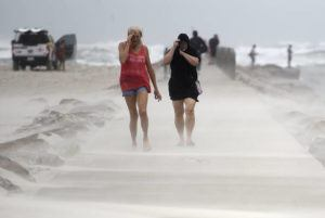 ANNIE RICE / CORPUS CHRISTI CALLER TIMES VIA AP                                 People shield their face from wind and sand ahead of Tropical Storm Nicholas Monday on the North Packery Channel Jetty in Corpus Christi, Texas. Lifeguards paroled the beach to warn people of the upcoming conditions.