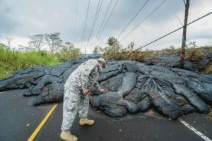 STAR-ADVERTISER / 2018                                 Jeff Hickman, a public affairs officer for the Hawaii National Guard, feels how hot the lava is after it crossed Pohoiki Road.