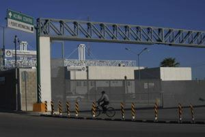 ASSOCIATED PRESS                                 A man rides his bike past the closed main entrance of the international border bridge that connects the cities of Del Rio, Texas and Ciudad Acuna, Mexico, on Sept. 24.