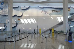 ASSOCIATED PRESS / MARCH 29                                 Pedestrians pass an art installation in a mural depicting New York City themes by Laura Owens, that adorns the open areas of Terminal B at LaGuardia Airport in New York.