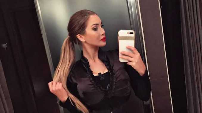 Pixee Fox in a beautiful black dress clicks a mirror selfie holding her highlighted hair.
