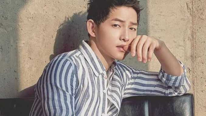 Song Joong-ki posing for a picture in a black-white shirt.