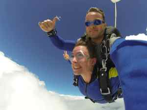 A selfie of a man and woman skydiving