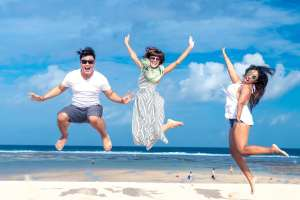 a man and two women jumping simultaneously on beach