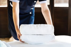 Room service personnel picking up rolled up towels