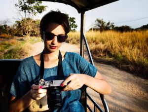 Woman holding a camera on a safari vehicle