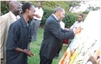 Uganda Prime Minister, Prof. Apollo Nsibambi signing one of Birutsya's paintings