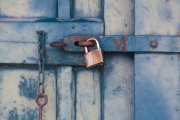 rustic blue door with gold and silver padlock locking door