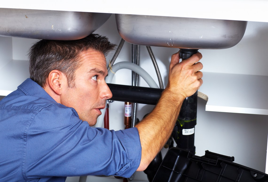 home solutions handsome plumber doing sink repair in kitchen