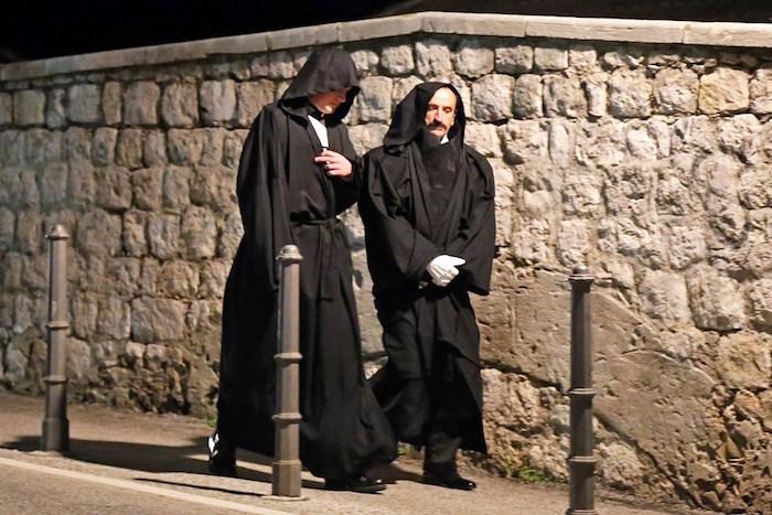 In het zwart geklede figuranten/acteurs? Of dragen ze slechts een zwarte overjas om hun daadwerkelijke kostuum te verbergen?