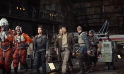 Jyn en Cassein lopen samen met een stel piloten en grondpersoneel een hangar uit.