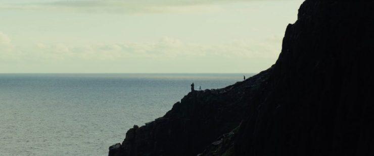 """En dan zien we een shot waar menig fan al heel lang op wacht. Rey die op de rotsen van Luke's eiland aan het trainen is met haar Lightsaber, terwijl Luke van een afstandje toekijkt. Ondertussen horen we in de voice over Luke """"It's so much bigger"""" zeggen."""