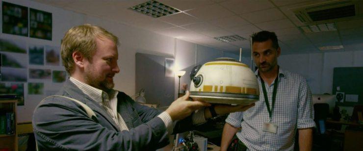 Regisseur Rian Johnson inspecteert een BB-8 hoofd onder het toeziend oog van BB-8 builder Josh Lee.