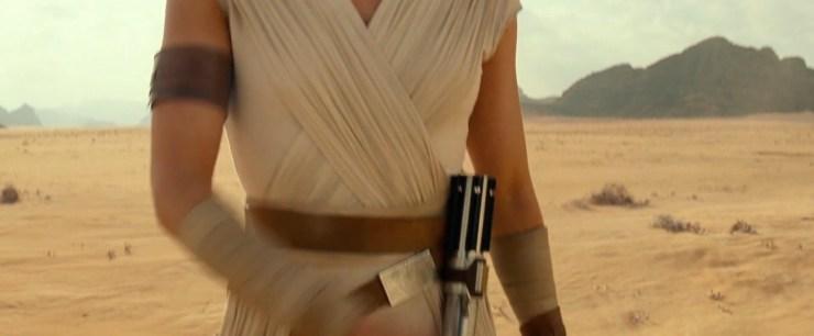 Vervolgens beweegt de camera omlaag en zien we Rey's lightsaber aan haar riem hangen. Het lightsaber dat ze van Luke geërfd heeft. Het lightsaber dat zij en Kylo Ren in tweeën getrokken hebben. Het lightsaber dat zij na The Last Jedi blijkbaar gerepareerd heeft. Er zit een nieuwe metalen ring op de plek waar het lightsaber gebarsten was, en los van een simpele reparatie heeft ze het hiermee een nieuwe stijl gegeven, een stijl die uitstekend bij Rey past.
