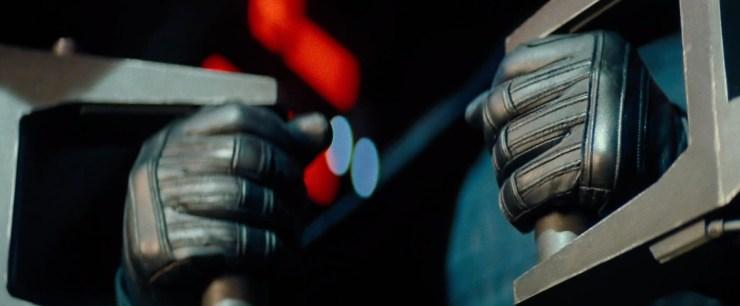 Handen in de cockpit van een TIE. Dit zijn dezelfde handschoenen als die Kylo Ren draagt en ook lijkt het figuur een zwarte cape over zijn armen te hebben hangen, dus het lijkt aannemelijk dat hij in zijn Silencer op Rey af stormt. Zijn handen lijken gespannen, is hij klaar om het vuur te openen?