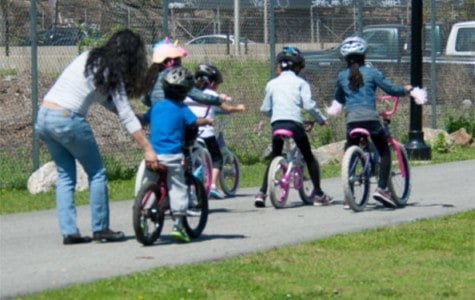 kids learn how to ride their bikes at a greenway in the park