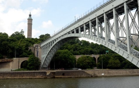 a bridge spans across to a park where a water tower exists