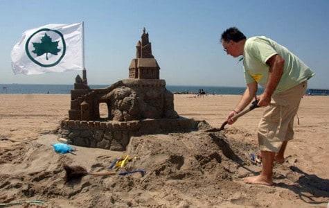 a man sculpts a sandcastle with a parks flag